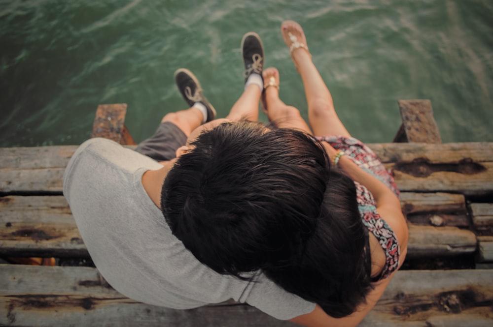 Hombre y mujer abrazándose en el muelle de madera marrón
